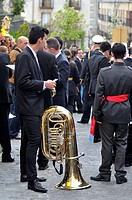 A man with a tuba waiting for the start of the Easter Procession in San Lorenzo de El Escorial (Madrid), Spain.