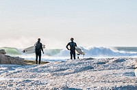 Surfers with boards survey the waves at Noord Hoek beach, Cape Peninsula, South Africa