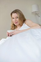 Pretty blonde woman with a cup in bed smiling at camera