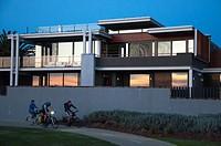 Cyclists passing a multi-million dollar luxury seaside home on Brighton´s ´Golden Mile´, Melbourne, Australia.