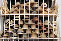 Street scene, hat shop display behind iron bars in window, Trinidad, Cuba