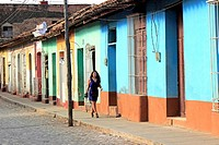 Attractive young woman walking on a colorful street in Trinidad, Cuba
