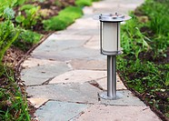 Solar-powered lamp on garden path. Nature background. Selective focus.