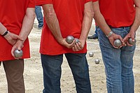 A team of petanque players watch their competition take its turn.