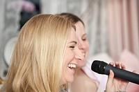 Girlfriends singing karaoke.