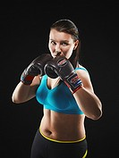 Boxing, young woman wearing a sportswear and she exercise, studio shot, black background.