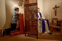 Hidden by a screen, a priest hears confession from a kneeling boy parishioner at a Laguna Niguel, CA, Catholic church. Note vestments. MODEL RELEASE.