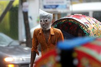 Rickshaw puller wears a plastic bag on his head and face as he carries passengers in a rain-soaked street of Dhaka, Bangladesh, 13 June 2015. City dwe...