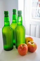 Three bottles of cider and three apples.