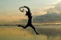 A woman with a scarf leaps on the beach in Newport, Oregon.