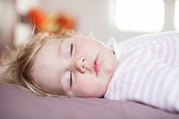 face of blonde caucasian baby nineteen month age with pink and white stripped jersey sleeping on brown sheets king bed.