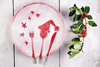 Representation of the Christmas holiday with cutlery on red dish and sprinkle with flour.