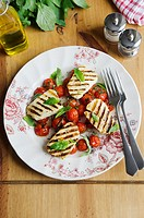 Halloumi and cherry tomato salad topped with basil.
