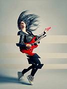 Woman rocker and an electric guitar, studio shot, cross processed image.