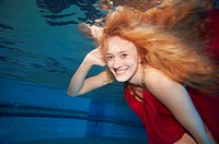 A young woman under water in a red dress