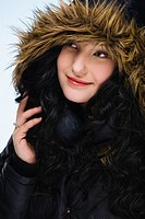 Beautiful girl wearing hood, light blue background, vertical format.
