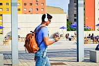 Young fashionable man with headphones, sunglasses and backpack walking while watching his smart-phone. Plaça de les Glòries Catalanes, Barcelona, Cata...