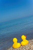 Two rubber ducks on Aegean beach.