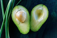 Cross section of an avocado halved with seed in tact, with a spring onion accent on greenish blue textured wooden background.