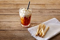 Coffee smoothie with wafers on vintage wood table.