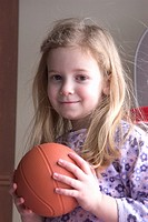 Young girl with long blond hair smiles as she holds a small basketball