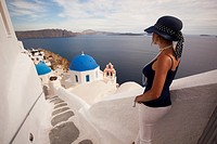 Woman in front of a blue domed church, Oia town, Santorini, Cyclades Islands, Greek Islands, Greece, Europe.