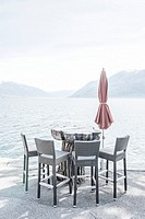 Chairs and a table with parasol on the waterfront on alpine lake Maggiore in Ticino, Switzerland.