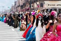 Young couples, costumed as â. . La Catrinaâ. . , a Mexican pop culture icon representing the Death, walk through the town during the Day of the Dead f...