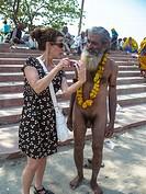 female tourist talks with naked naga sadhu during kumbh mela in haridwar, india