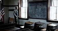 Man dressed as a school teacher inside an Abandoned Scholl house at sunset in Kansas.