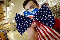 14 yr old boy with American flag, or bunting, in supermarket, Sharon, Connecticut, USA