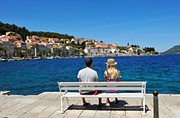 young couple sitting on a bench on the promenade Obala Franje Tudmana, Korcula old town, Korcula island, Croatia, Southeast Europe.