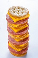 Tower of stacked crackers, cheese, and salami on white background.