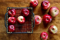 Birds eye view of several Apples scattered, inside and outside a basket on wood background.