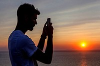 A young man filming sunset on his cellphone, Oia, Santorini, Greece.