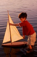 Boy, standing nearly knee deep in water, playing with toy sailboat in Upper Mystic Lake in Medford, MA, model released mr_5215.