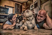 Middle aged couple on floor of kitchen with their two boxer dogs, one being kissed