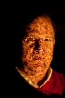 Portrait of man illuminated by fiber optic light source, where dark spots indicate broken fibers in the bundle