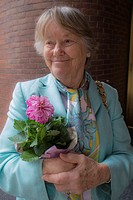 Portrait of elder woman wearing silk scarf and holding a bouquet of cut flowers.