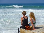 Two women watching breaking waves at the shore of Ericeira, Atlantic coast, Region Centro, Portugal, Europe.