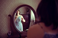 Young woman dressing in front of a vanity mirror.