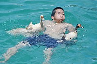 Itoman, Okinawa, Japan: a young man has caught two ducks during the traditional Haarii Boat Festival