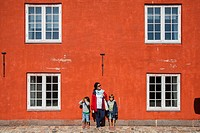 Mother and two child on a red wall. Kastellet, Copenhagen. Denmark.