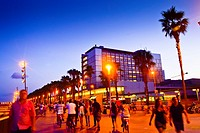 People walking along Passeig Maritim at sunset. Hospital del Mar building in background. Barceloneta quarter, Barcelona, Catalonia, Spain.