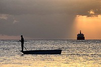 Africa, Mauritius, Western Coast, sunset near Port Louis, sunset with single fishermen boat and distant ship