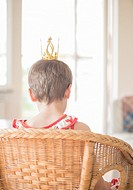Little girl playing princess at home in living room. Concept of childhood, aspirations and innocence.