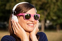Woman listening music in park.