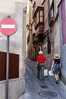 Spain, Europe, Spanish, Hispanic, Toledo, narrow steep street alley, buildings, residences, man, woman, couple, exploring,