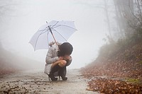Young woman squatting under umbrella alone and lost