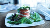Plated Caprese Salad with Balsalmic drizzle on mixed Mescaline Salad in clean kitchen environment with window light. Shot at a restaurant in San Juan,...